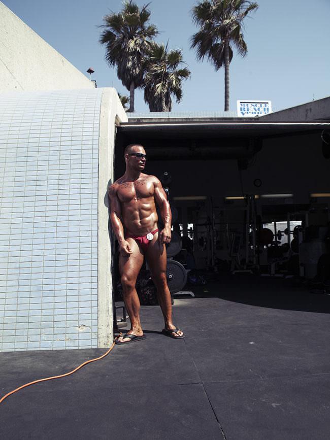 Muskulöser Mann steht im Kontrast an einer Mauerecke.