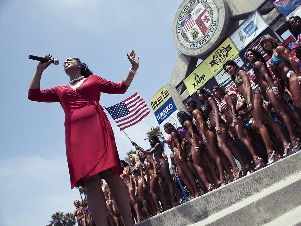 Bei einem Event spricht eine Frau in rotem Kleid in ein Mikrofon. Hinter ihr eine Amerika Flagge und aufgereihte Frauen im Bikini.