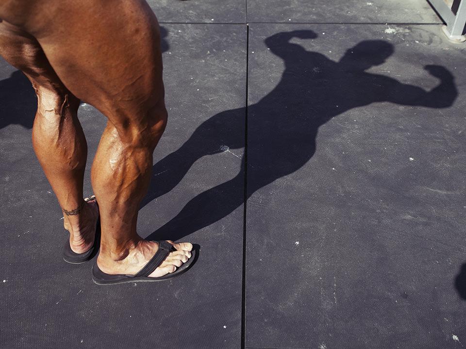 Ein Mann zeigt seine Muskeln, man sieht nur seine echten Beine und seinen ganzen Körper als Schatten.