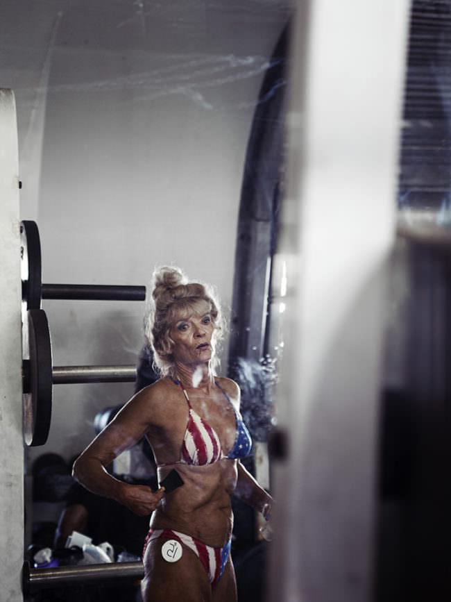 Trainierte ältere Frau steht in einem Amerika Bikini im Raum und posiert für die Kamera.