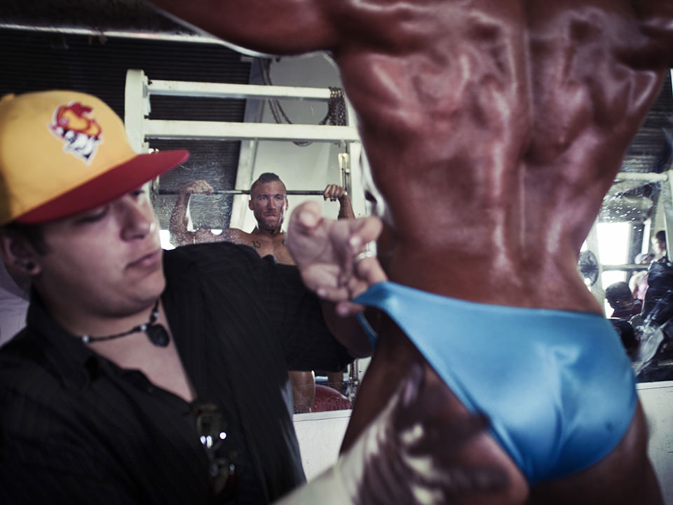 Mann mit Cap ölt einen Sportler in Kampfhose ein.