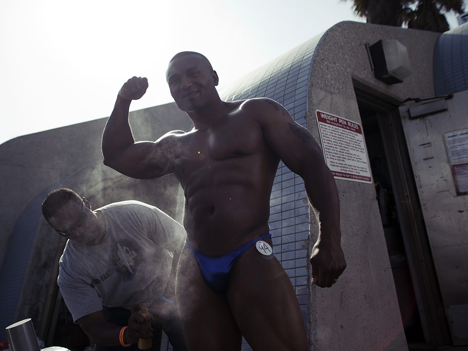 Muskulöser Schwarzer zeigt stolz seine Armmuskeln.