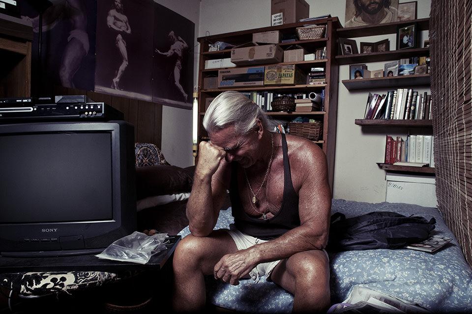 Mann im Muskelshirt und mit ergrauten langen Haaren sitzt auf einem Bett, scheinbar Niedergeschlagen.