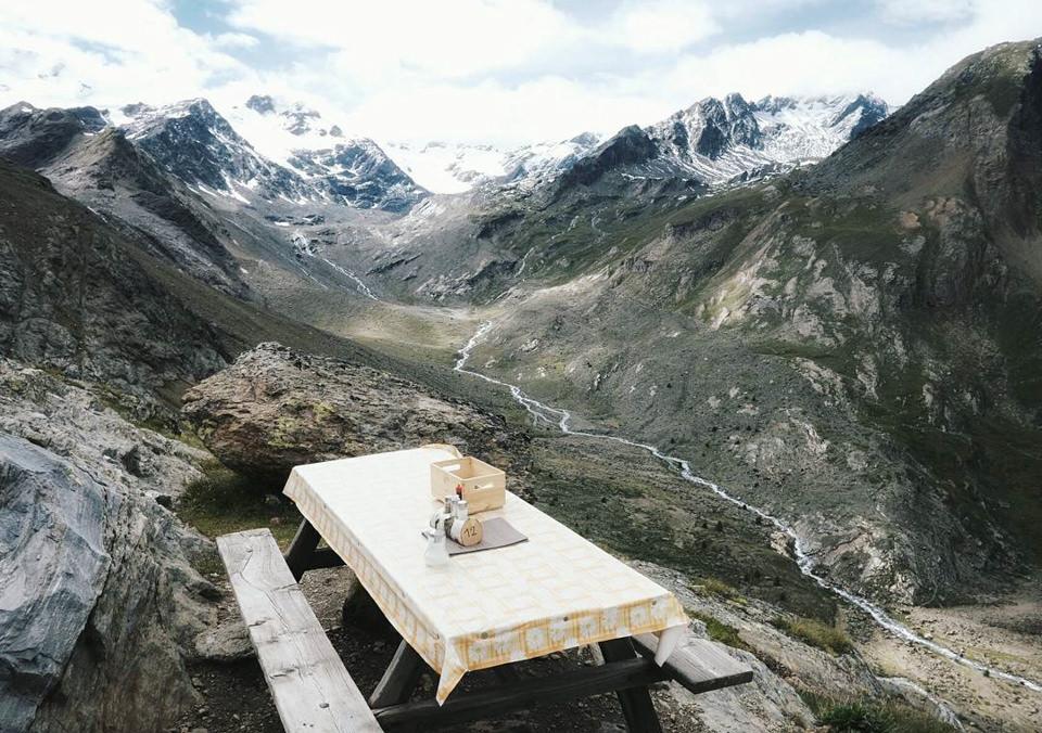 Holztisch und Holzbänke inmitten einer Berglandschaft