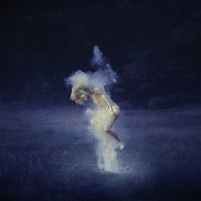Eine Frau springt mit weißem Pulver