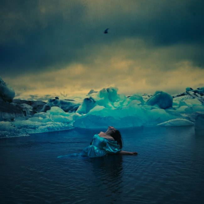 Eine Frau schwimmt zwischen Eisschollen im Meer
