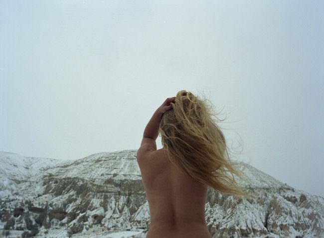 Eine nackte Frau vor verschneiten Bergen