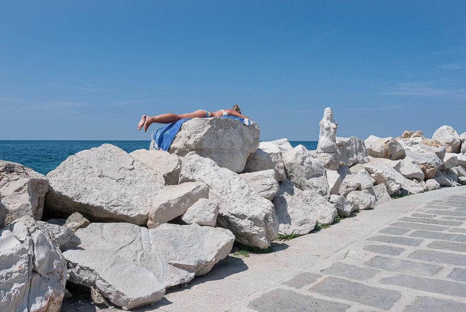 Eine Frau sonnt sich auf Steinen
