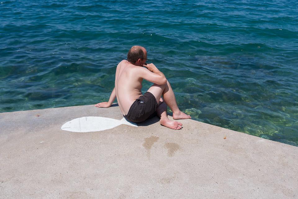 Ein Mann sitzt auf Beton mit Blick aufs Meer