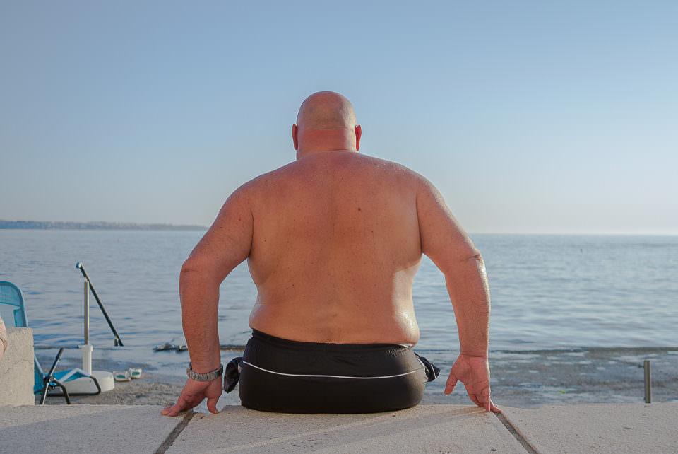 Ein Mann sitzt am Meer