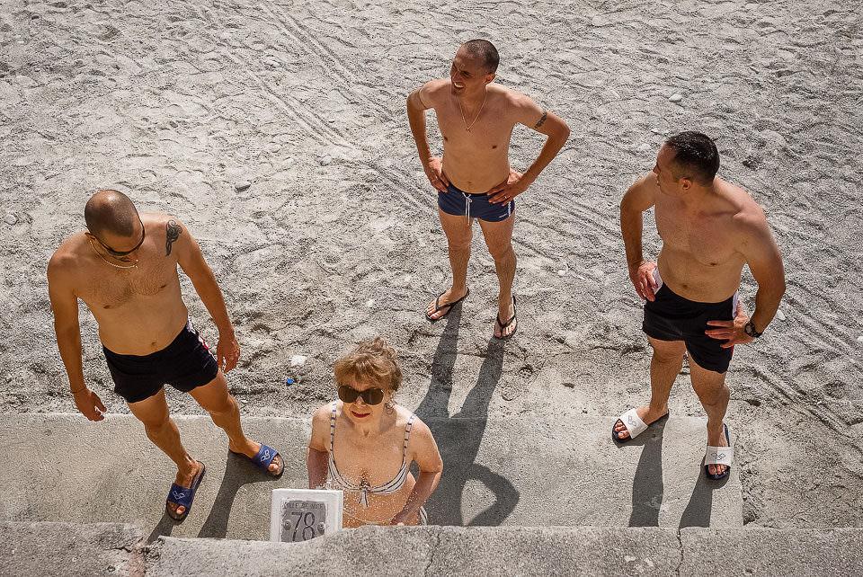 Menschen warten auf eine Dusche am Strand