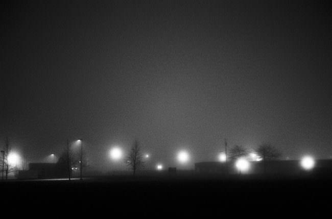 Eine dunkle Straße mit hell leuchtenden Straßenlaternen