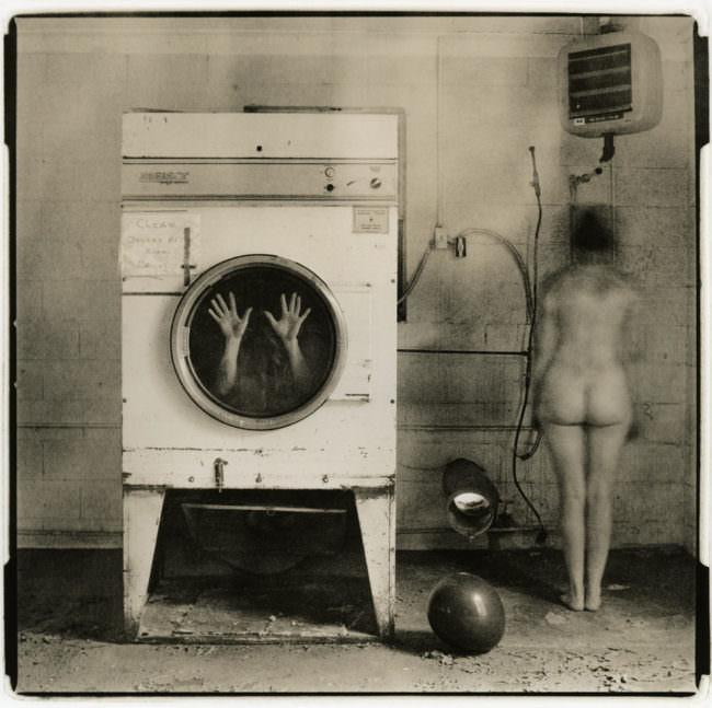 Eine Frau steht nackt neben einer Waschmaschine, in der Hände sichtbar sind