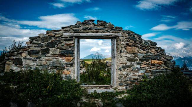 Eine Ruine durch deren Fenster Landschaft zu sehen ist