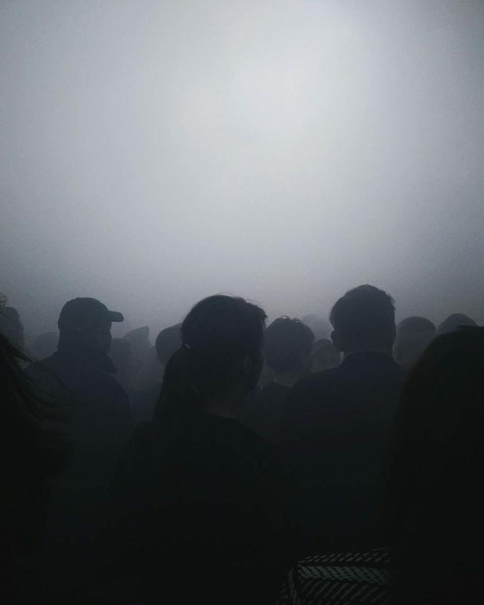 Umrisse einer Menschenmenge von hinten im Nebel