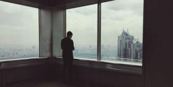 Ein Mann der aus dem Fenster eines Hochhauses auf eine Stadt blickt.