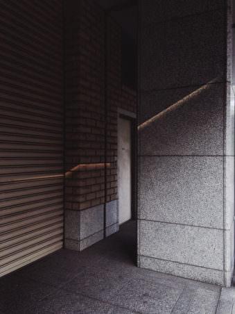 Eine Säule aus Beton vor einem Rolltor.