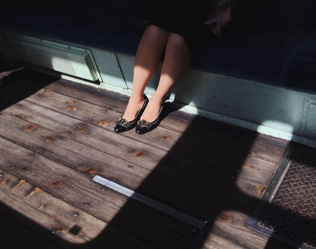 Die Füße einer Frau die auf einer Bank sitzt und zur hälfte von der Sonne angestrahlt werden.