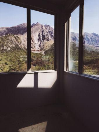 Der Blick aus dem Fenster eines Gebäudes auf eine Bergkette.
