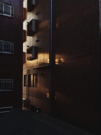 Die Flucht zwischen Backsteingebäuden in die ein einzelner Sonnenstrahl dringt.