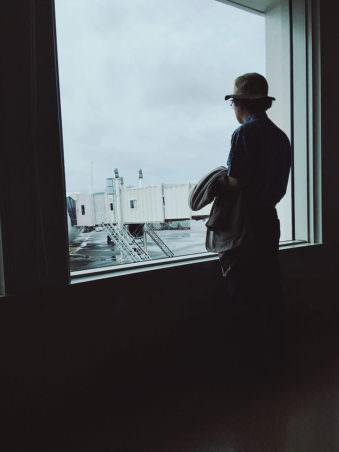 Ein Mann mit Hut steht an einem Terminal am Flughafen und blickt aus dem Fenster