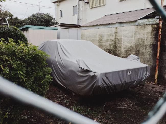 Ein Auto unter einer grauen Abdeckung in einem Hinterhof.