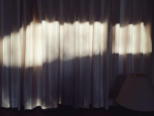 Ein Sonnenstrahl, der auf einen Vorhang trifft.