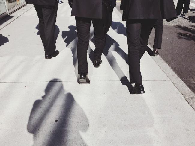 Männer in Anzügen laufen über eine Straße, es sind nur die Beine der Männer im Bild.