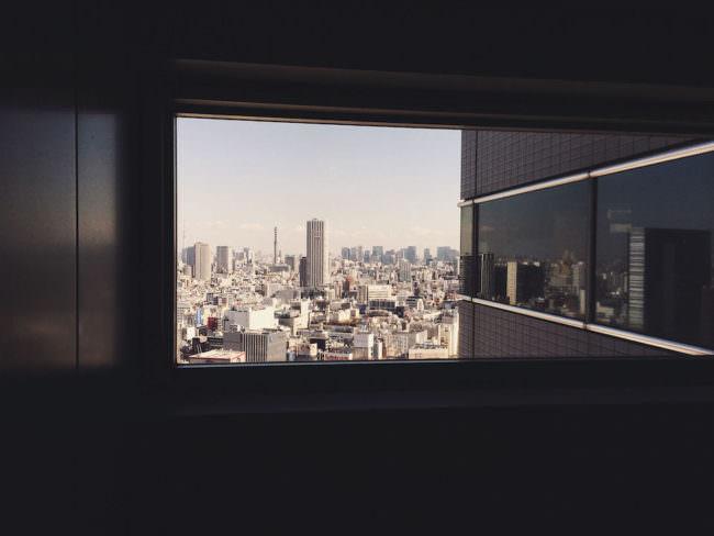 Der Blick auf eine Skyline aus dem Fenster eines Wolkenkratzers.