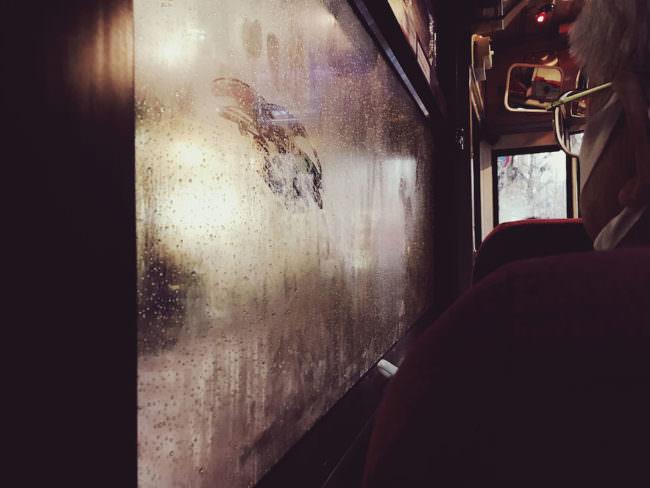 Blick über die Schulter einer Frau auf eine beschlagene Scheibe in einem öffentlichen Verkehrsmittel.