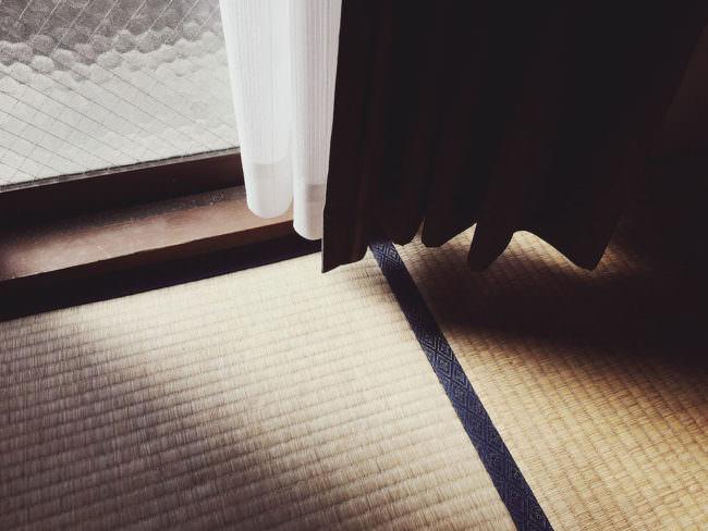 Der Blick Richtung Boden auf die Ecke eines Vorhanges auf den ein Sonnenstrahl trifft.