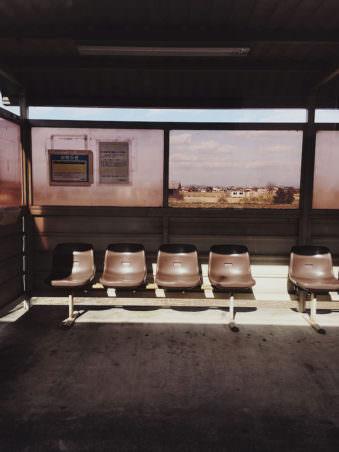 Eine Bushaltestelle, teils in der Sonne, teils im Schatten.
