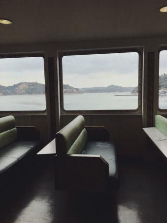 Der Blick aus dem Fenster eines Bootes auf eine Felsige Küste.