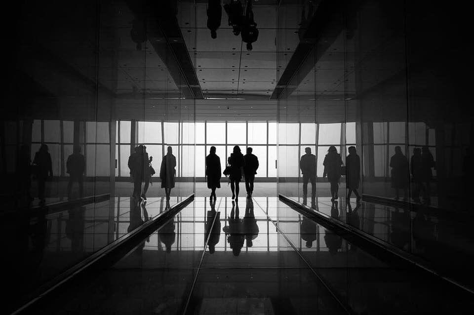 Menschen in einem sich spiegelnden Gang