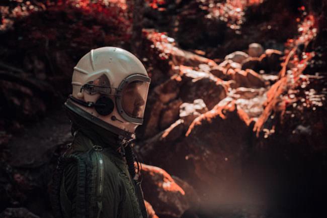 Oberkörperportrait eines Astronauten, der vor einer roten Felswand steht.