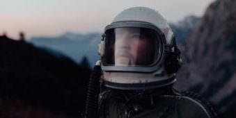 Portrait eines Astronauten vor einer Berglandschaft.