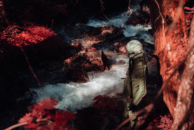 Ein Astronaut steht neben einem Fluss in einer roten Felslandschaft.