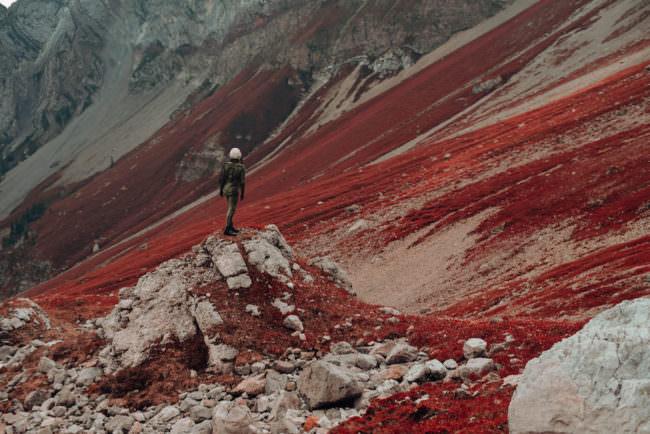 Ein Astronaut steht auf einem Geröllhügel in einer roten Felslandschaft.