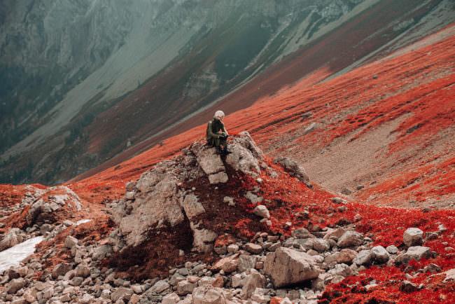 Ein Astronaut sitzt auf einem Haufen Geröll vor einer roten Felslandschaft.