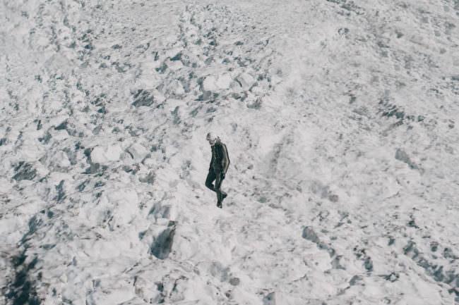 Ein Astronaut geht durch eine Schneelandschaft.