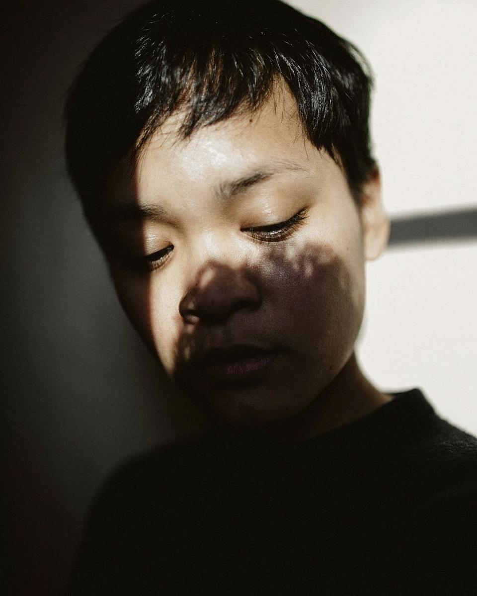 Portrait einer Frau mit kurzen Haaren, deren Gesicht von Licht und Schatten umspielt wird