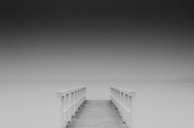 Ein Steg der auf einen See hinausführt, der durch eine Langzeitbelichtung glatt wirkt.