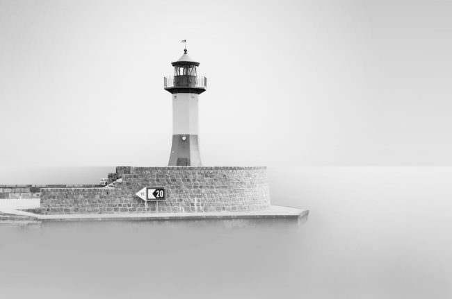 Ein Leuchtturm vor einem See, dessen Wasser durch Langzeitbelichtung weich wirkt.
