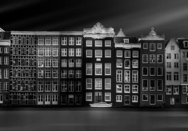 Ein Schwarzweissbild einer Häuserfassade vor einem Fluss.
