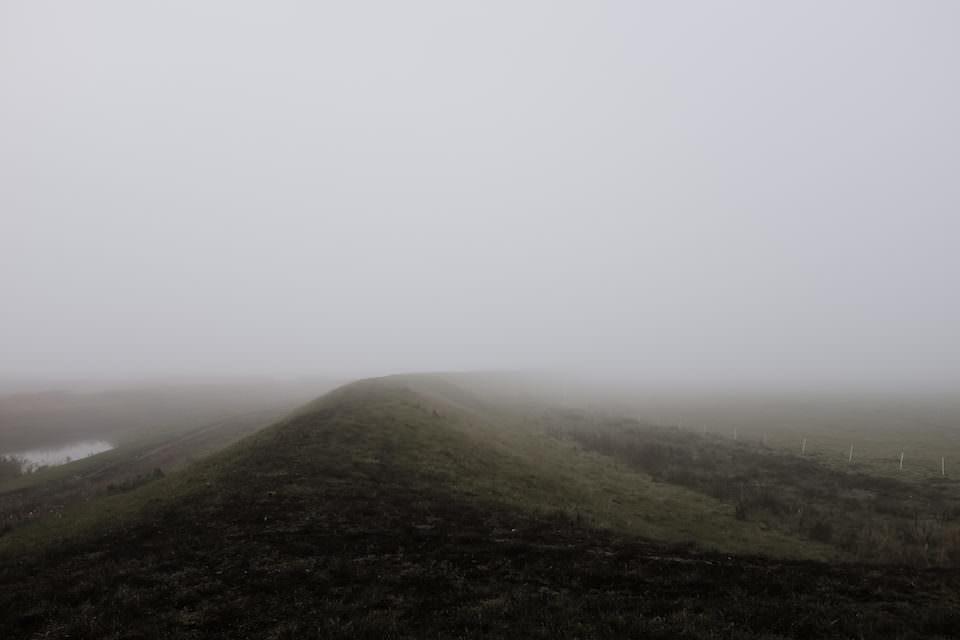 Minimalistische Landschaftsaufnahme eines Hügels im Nebel.