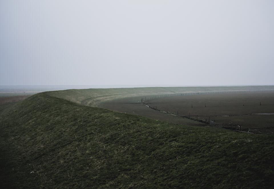 Minimalistische Landschaftsaufnahme eines Dammes im Nebel.