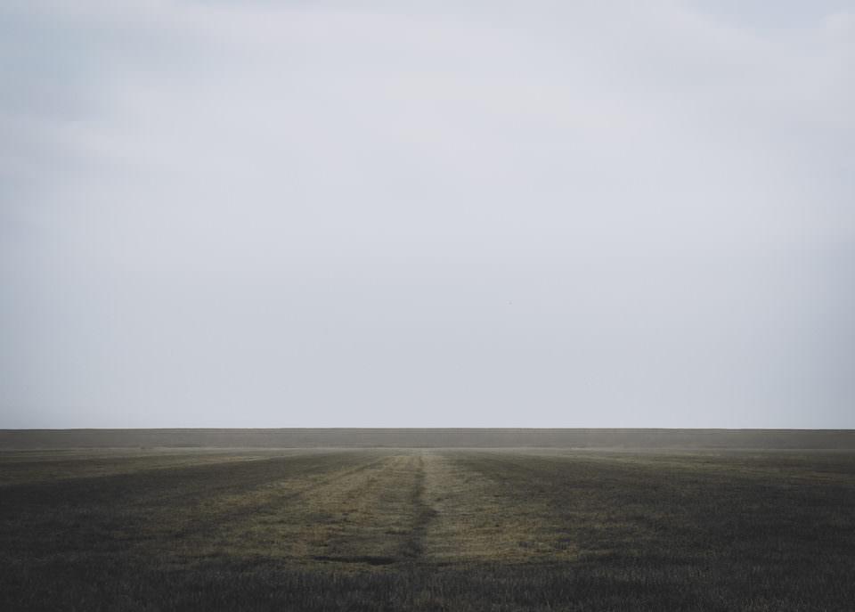 Minimalistische Landschaftsaufnahme eines Feldes im Nebel.