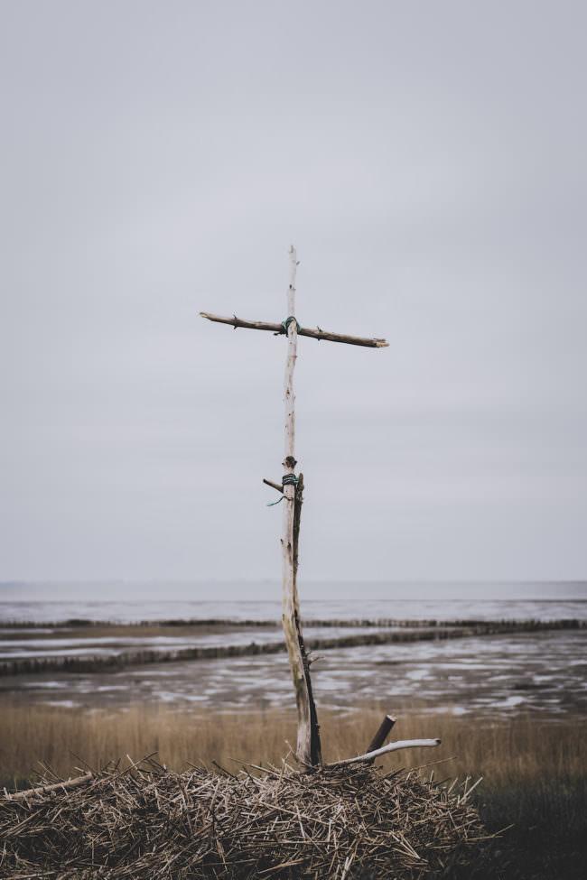 Ein Kreuz aus Ästen, das vor einem Strand aufgestellt wurde.