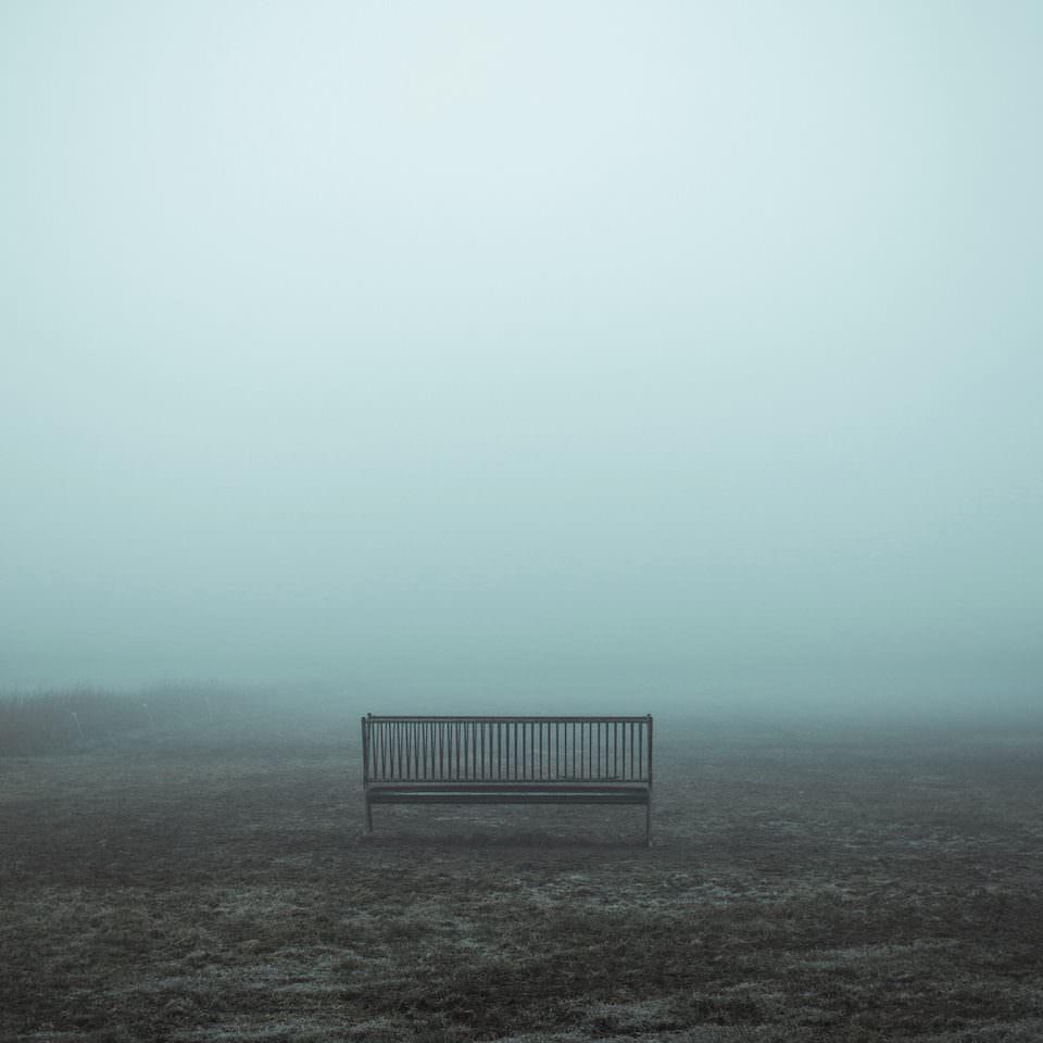 Minimalistische Aufnahme einer Bank im Nebel.