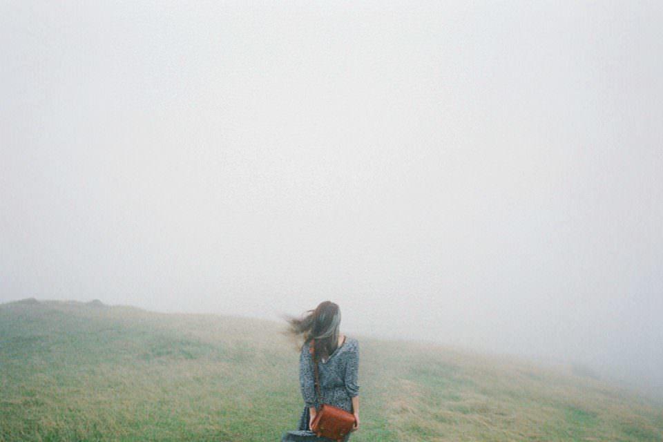 Eine Frau steht vor einem nebligen Hügel und blickt weg von der Kamera.